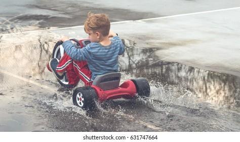 Young Boy Riding a Big Wheel Bike Through a Puddle