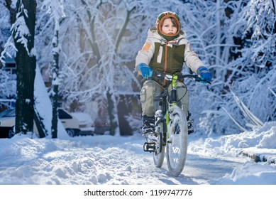 Young boy riding bike in beautiful winter city