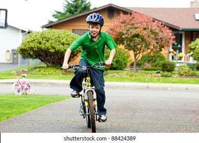 A young boy riding his bike on a driveway wearing a helmet.