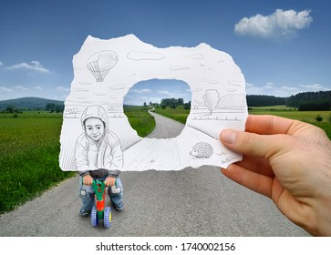 Young boy riding a small tricycle sketched on a hand held piece of paper with vanishing path and green countryside scenery in the photo background. Mixed media image.