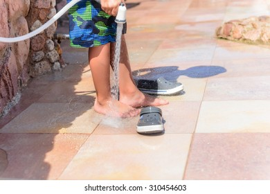 Young boy rinsing off his feet and shoes to get rid of the salt and sand after spending the day at the beach at a seaside resort on summer vacation
