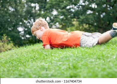 A young boy rolling down a hill