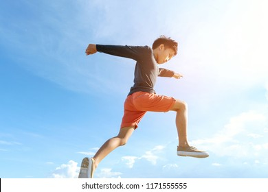 Young boy run and jump over a weeds during blue sky in summer.