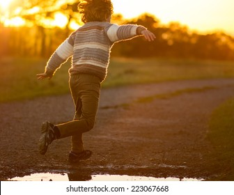 a young boy running with arms outstretched jumping over a puddle at sunset