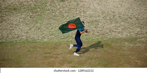 Young boy running with a Bangladeshi national flag around a field