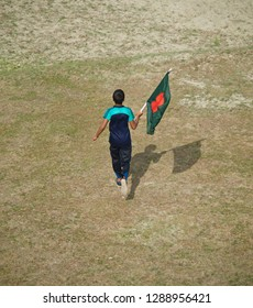 Young boy running in a field holding the Bangladeshi national flag