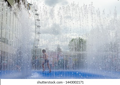Young boy running inside a fountain to cool down from the hot summer heat, London, England.