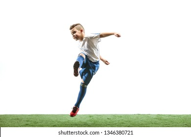 Young boy running and jumping isolated on white studio background. Junior football soccer player in motion
