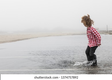 A young boy is running and splashing in a large puddle in a flooded parking lot. The boy is wearing waterproof galoshes in the deep water as he jumps and skips in the puddle in the spring after storms
