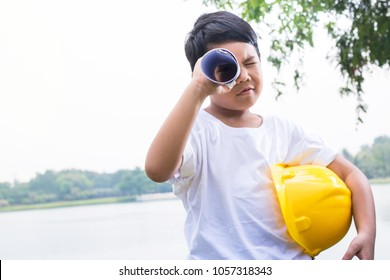 Young boy with and safety helmet spying on someone through the rolled sheet of white paper as a telescope