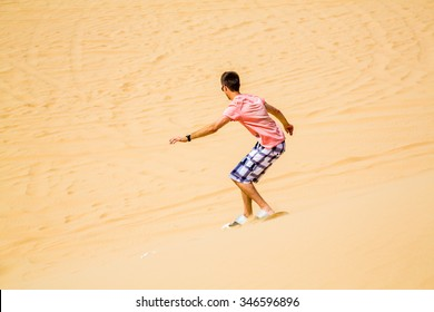 Young boy sand boarding down the dune in a desert near Emirates
