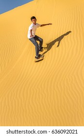 Young boy sand-boarding on a sand dune