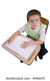 Young boy at school desk writing with book and pencils isolated over a white background