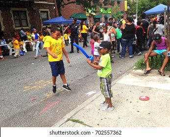 A young boy seems to lift another with a balloon sword during a street party on Carroll Street in Crown Heights, Brooklyn, NY in August 2016.