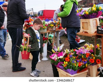 Young boy selects flower to buy for his mother at a pop-up flower stand on the sidewalk in Cluj-Napoca, Romania - March 7, 2019