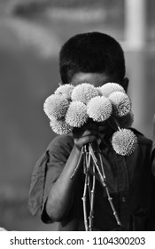 A young boy is selling flowers on the street unique black and white stock photograph