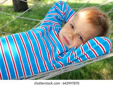 A young boy in a sentimental mood lies in a hammock.