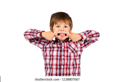 A young boy, with shaggy hair, makes a funny face with his tongue sticking out.  He is wearing a plaid shirt and is on a white background, isolated, with a clipping path.  Copy space.