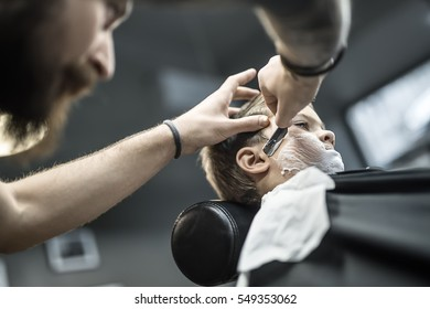 Young boy with a shaving foam on the face in the barbershop. He wears a black salon cape. Bearded barber with a tattoo is shaving boy's face with the help of the straight razor. Low aperture photo.