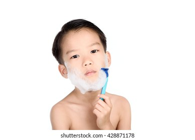 Young boy is shaving his face in the bathroom.