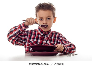young boy in shirt slurping soup at table