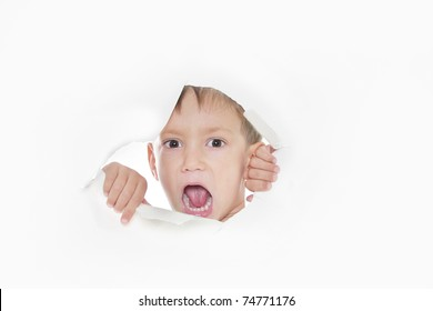 young boy shouting loudly through hole in paper