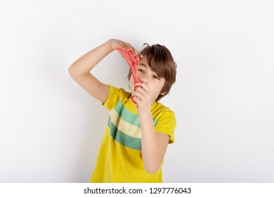 Young boy showing a red slime looks like gunk between his hands