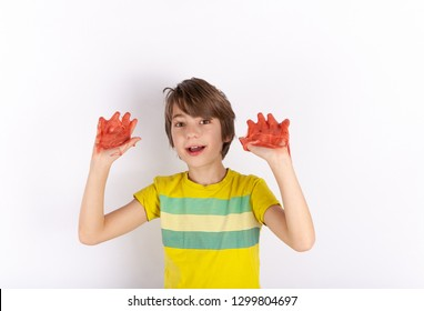 Young boy showing red slime on his hands