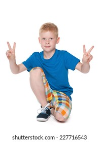 A young boy shows a victory sign against the white background