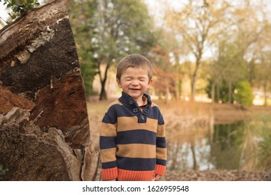 Young boy with silly face. Lake in background. Fall leaves