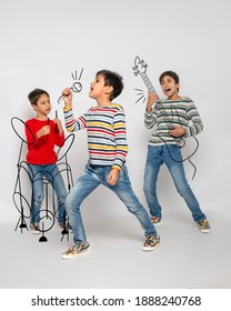 A young boy sings into an imaginary microphone, two guys emotionally plays an imaginary guitar and percussion instruments against grey background in studio