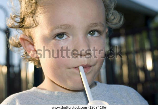 Young boy sipping from straw while outdoors
