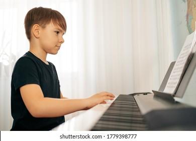 Young boy sitiing at digital piano. Playing keyboard, focused kid have activity at home. Hobby