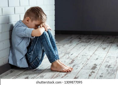 A young boy sits alone with a sad feeling at school near the wall. Offended child abandoned in the corridor and bent against a brick wall. Bullying, discrimination with copy space.