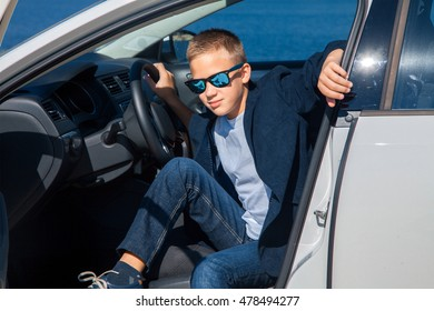 young boy sits in the car and looking at the camera in sunglasses