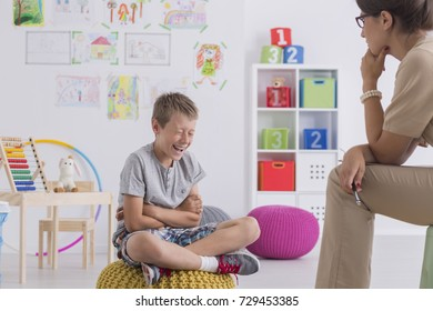 Young boy sits on a yellow pouf and laughs while consulting a school psychologist