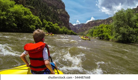 A young boy sits at the very front of the raft known as: riding the bull in the Colorado River during a white water rafting expedition through Glenwood Canyon