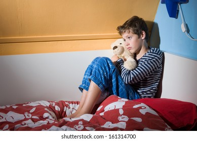 A young boy is sitting afraid and depressed on his bed in his bed room