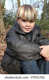 Young boy sitting in an autumnal forest