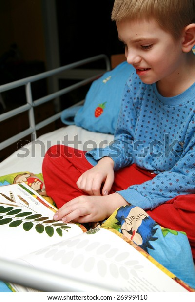 Young boy sitting in the bed with pajamas and reading book about plants. Evening in the child room.