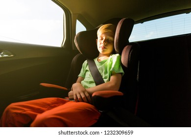 Young boy sitting in a car seat for children
