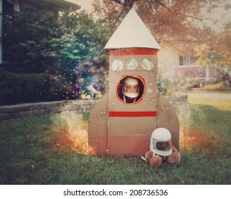 A young boy is sitting in a cardboard space rocket ship with an astronaut helmet on. He is in the front yard imagining he is in space with stars.