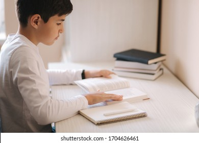 Young boy sitting at desk read the book and whright down in notebook. Study at home during quarantine