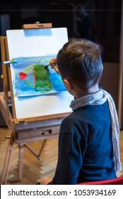 Young boy sitting in front of easel painting a fish, holding a brush in hand
