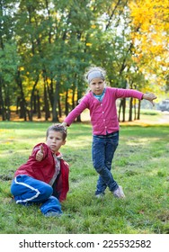 Young boy sitting grass, showing thumb up and pretty girl thump down in autumn park