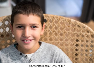 Young boy sitting in the knitted chair, looking at camera and smiling