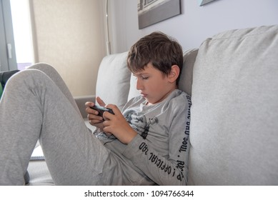 Young boy sitting in living room watching to his smartphone