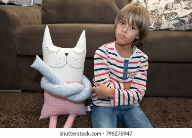 Young boy sitting on the floor with favorite cat pillow, with crossed hands and angry face