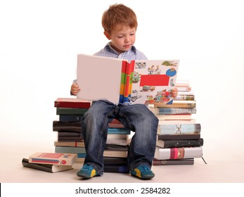 Young boy sitting on a pile of books reading against a white background