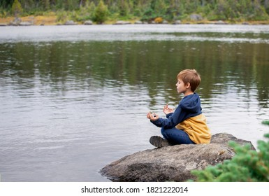 Young boy sitting on a rock by a rural lake practising peaceful yoga with his eyes closed.